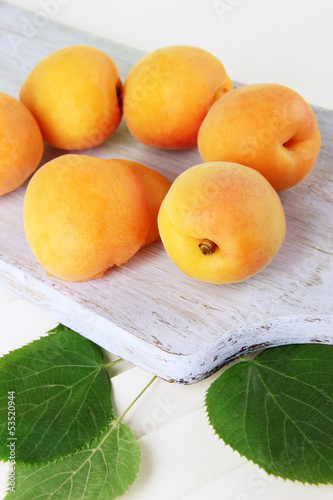 Apricots on board on wooden table
