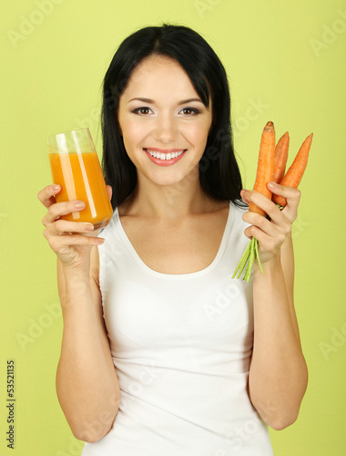Girl with fresh carrot and juice on green background