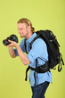 Handsome photographer with camera, on green background