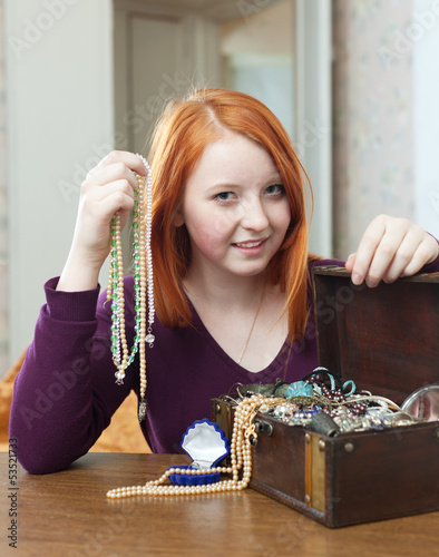 teen girl looks jewelry