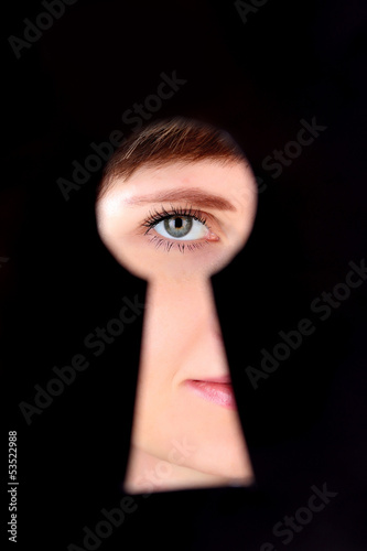 Woman eye looking through hole in keyhole, on black background