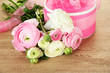 Ranunculus (persian buttercups) and gift on wooden background