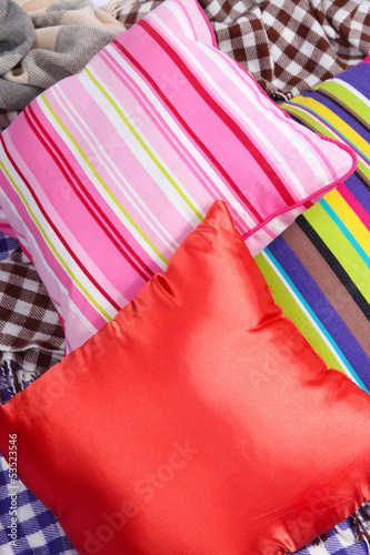Three bright various pillows on plaid