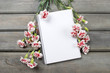 Top view of blank sheet of notebook among pink carnation flowers
