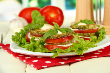Tasty roasted marrow and tomato slices with salad leaves,