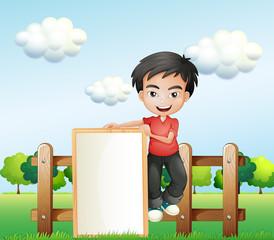 A boy holding an empty framed signboard