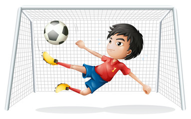 A boy playing soccer wearing a red uniform