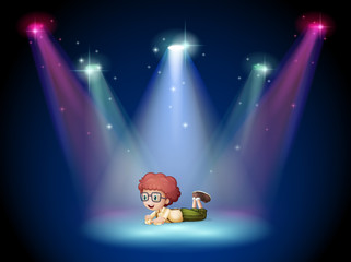A boy lying in the middle of the stage with spotlights