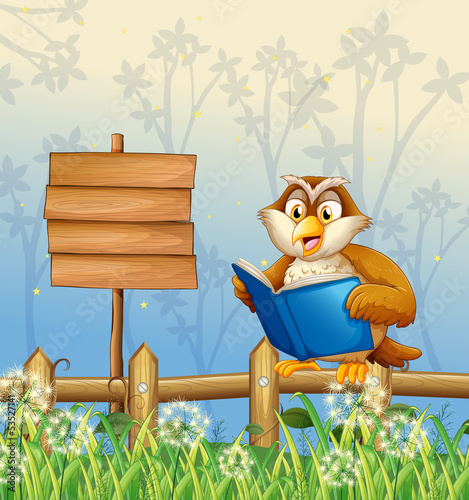 Wall mural An owl reading a book beside a wooden signboard