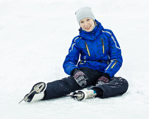 Woman sitting on ice skates.