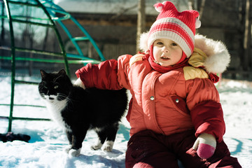 Funny happy child playing with cat.
