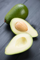 Two avocados: one whole and one cut, close-up