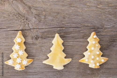 three christmas tree cookies on wood brackground