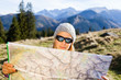 Woman hiker reading map in mountains