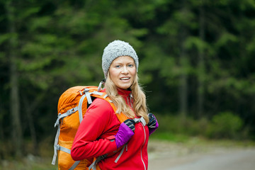 Woman hiker with backpack hiking in forest