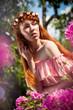 Красивая девушка в парке среди цветов