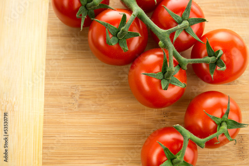 Cherry tomatoes on the vine against wooden cutting board