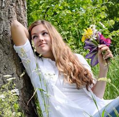 Junge, glückliche Frau genießt den Sommer unter Baum