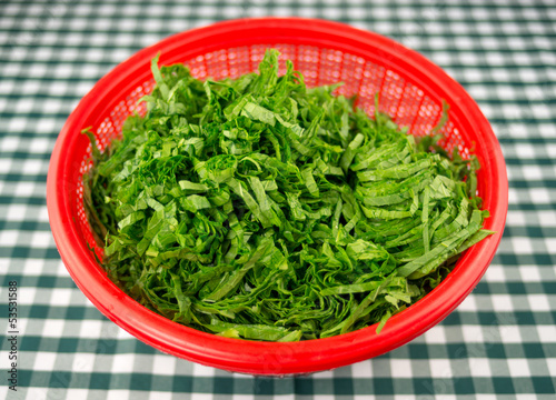Chopped mustard greens in a red strainer bowl