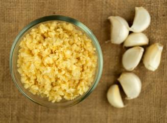 Closeup of chopped garlic in a glass bowl