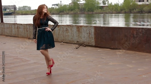 beautiful girl posing on an old barge on the river