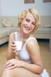 Blonde Frau trinkt Mich aus einem Glas
