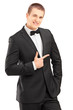 Handsome stylish male in bow tie suit pointing