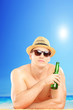 Smiling guy with hat and sunglasses drinking cold beer on a beac