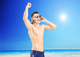 Excited man listening music and gesturing happiness, on a beach