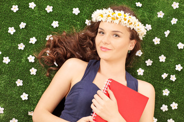 Beautiful young woman with a daisy hair wreath lying on a grass