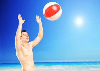 Young male playing with a beach ball, next to a sea