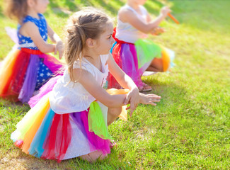 Young girls dancing during a preschool performance outdoor