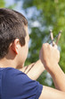 Boy with a slingshot aim to the tree