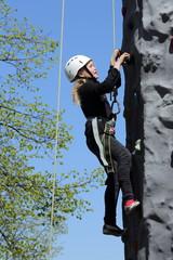 Mädchen mit Helm an Kletterwand