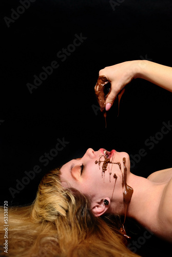The girl covered with hot chocolate lies on a black background
