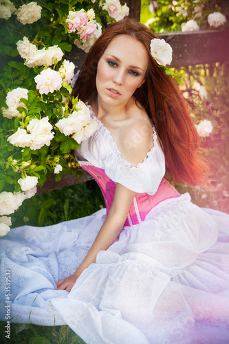Красивая рыжеволосая девушка среди цветов