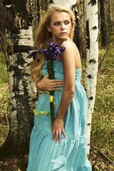 Beautiful blond woman with blue flowers walking in a forest
