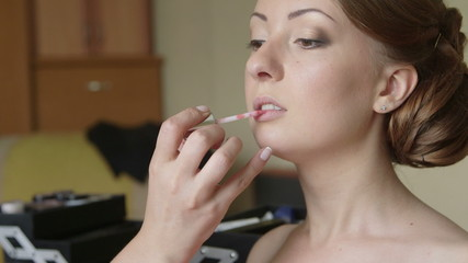 Bridal makeup artist applying lip gloss