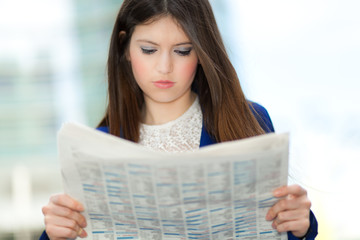 A young pretty business woman reading the newspaper