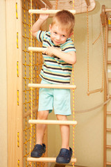 Little child climbing on rope ladder.