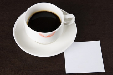Cup of coffee with lipstick mark and blank paper note for text