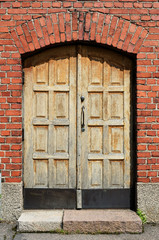 large yellow door in brick wall