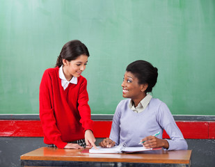 Schoolgirl Pointing On Paper While Teacher Looking At Her