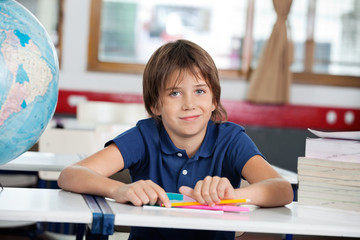 Little Boy Smiling While Sitting With Globe And Books At Desk