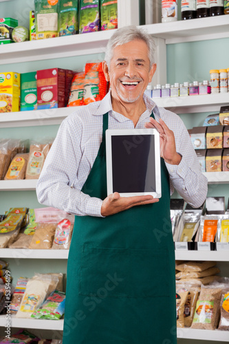 Male Owner Showing Digital Tablet In Store