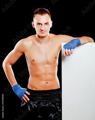 Young handsome boxer man standing near board