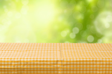 Empty table coved with tablecloth over bokeh garden