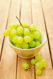 Grapes in bowl over wooden background
