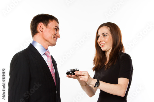 young man and woman are holding a toy car
