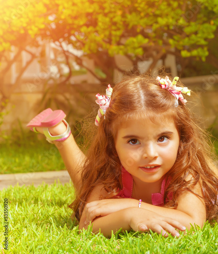 Little girl lying down on green grass